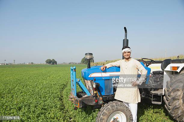 Farmer standing near a tractor in the field, Sonipat, Haryana, India