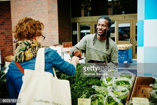 Farmer taking credit card from customer