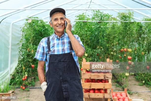 Farmer talking on smart phone in greenhouse