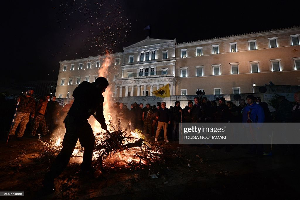 A farmer throws branches on a fire burning in front of the Greek parliament in Athens during a rally against pension reform on February 12, 2016. Fears that Greece will exit the eurozone, a 'Grexit', could revive if Greek authorities do not come up with 'credible' reforms, notably on pensions, a senior IMF official said on February 11, 2016. / AFP / LOUISA GOULIAMAKI