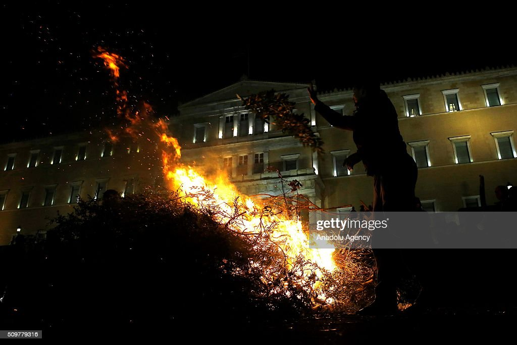 A farmer throws branches on fire during a rally against pension reform in front of the Greek parliament at the Syntagma Square in Athens on February 12, 2016.