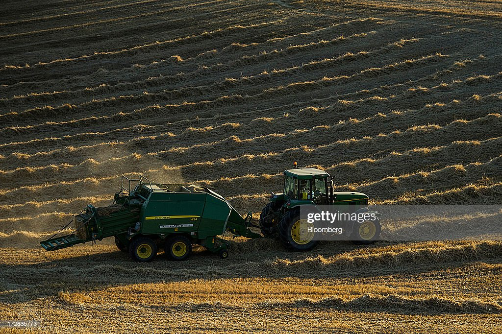 A farmer uses a John Deere 1424 baler machine to make a hay bale following a harvest in Cervera, Spain, on Thursday, July 4, 2013. Spain consumes about 28 million to 30 million tons of grain a year, of which two-thirds is produced domestically, according to young farmers organization Asaja. Photographer: David Ramos/Bloomberg via Getty Images