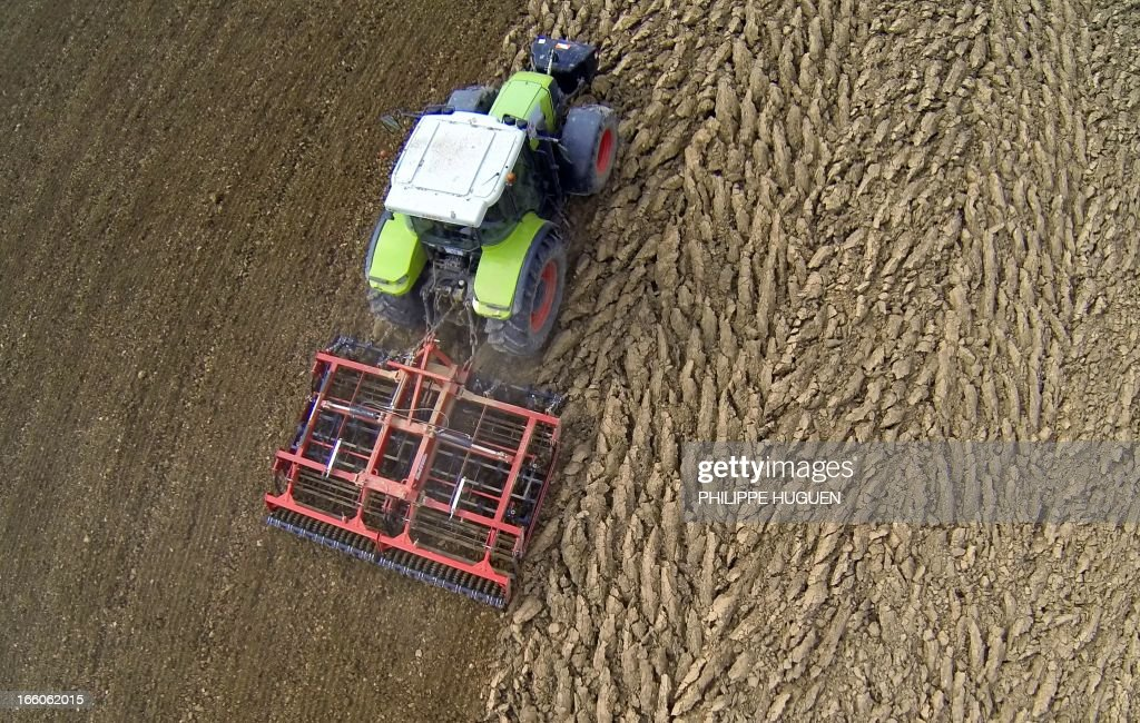 A farmer uses a tractor to plough a field near Godewaersvelde on April 8, 2013. AFP PHOTO / PHILIPPE HUGUEN