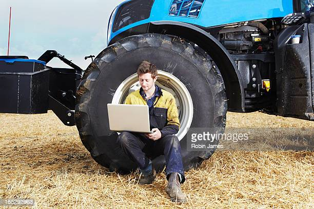 Farmer using laptop in field