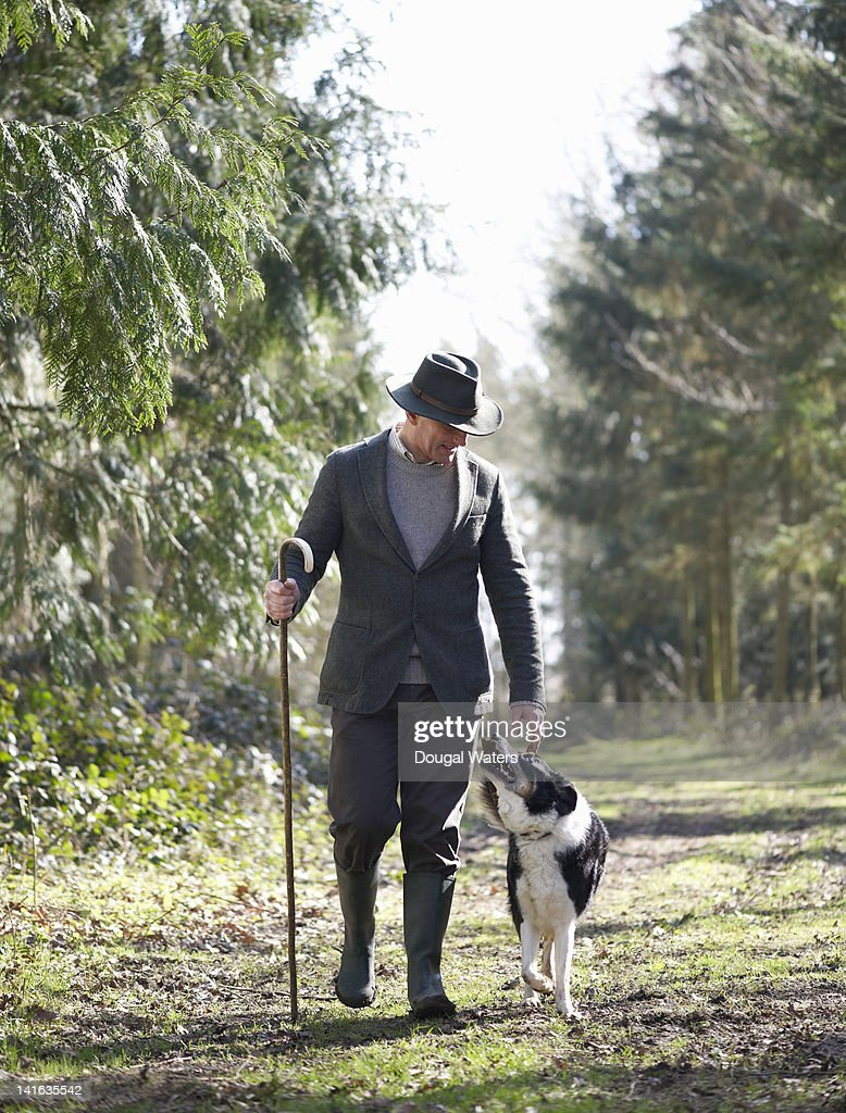 Farmer walking in countryside with dog : Stock Photo