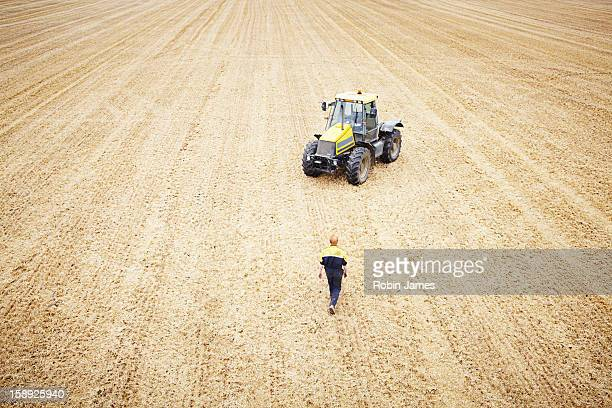 Farmer walking to tractor in crop field