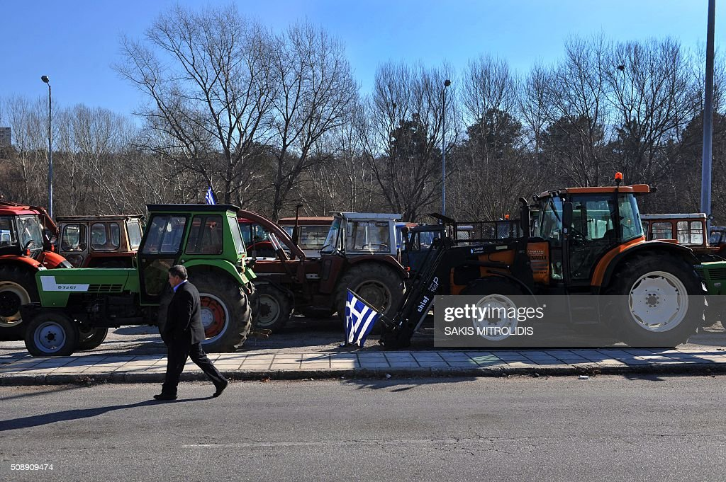 A farmer walks past tractors parked at the customs post at the border crossing of Promachonas between Greece and Bulgaria, in northern Greece, as farmers set up a blockade of customs offices, shutting down the movement of trucks to and from Bulgaria on February 7, 2016. Greek farmers protesting against pension reforms heightened highway and border protests around the country, piling pressure on the leftist government of Prime Minister Alexis Tsipras. The mobilisation which began in mid-January has created tractor blockades at dozens of highway locations and key border crossings to Bulgaria and Turkey, which the farmers intermittently open for a few hours each day. / AFP / SAKIS MITROLIDIS
