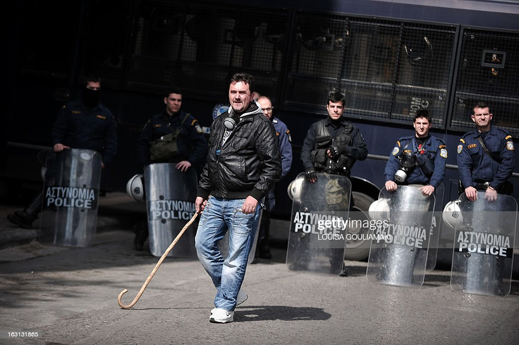 A farmer walks with a cane by a police blockade in front of the agriculture ministry in Athens during a rally by farmers' unions from all over Greece on March 5, 2013. Over 2,000 Greek farmers gathered in Athens to demand lower taxes, arguing that the rising cost of fuel and electricity was driving them to ruin.The farmers also called for subsidies from the heavily indebted state, which has been forced to undertake a tough austerity policy, to help them lower their costs and remain competitive.