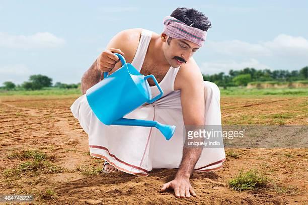 Farmer watering soil in a field