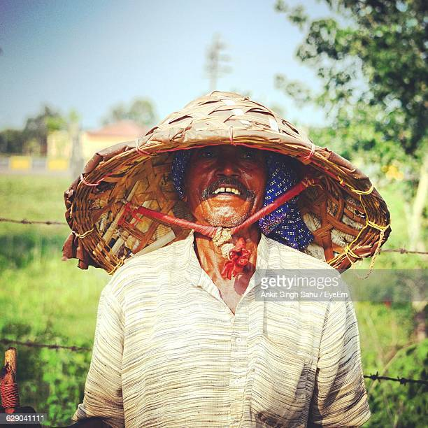 Farmer Wearing Asian Style Conical Hat On Field