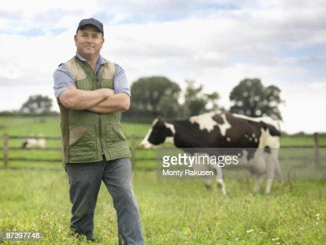 Farmer With Cow In Field