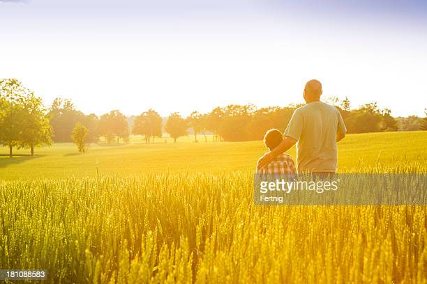 Farmer with his son at sunset