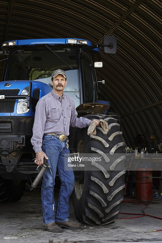 Farmer with Tractor in Workshop : Stock Photo