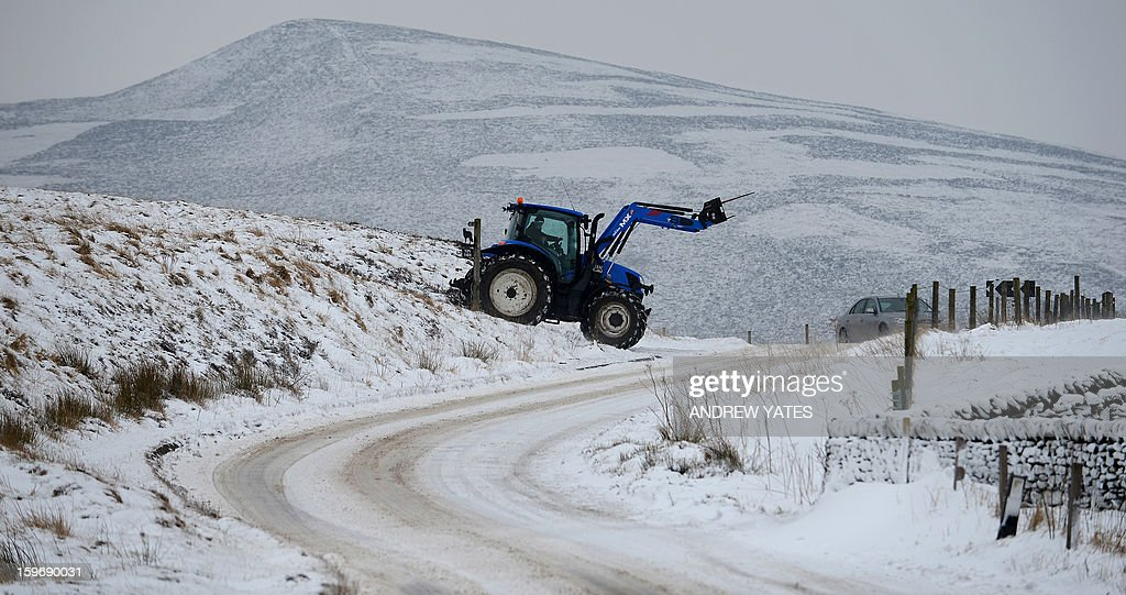 A farmer works in the snow on hills above Hayfield in the Peak district, northern England, on January 18, 2013. Snow swept across Britain on Friday, forcing airports to cancel dozens of flights and more than 2,000 schools to close.