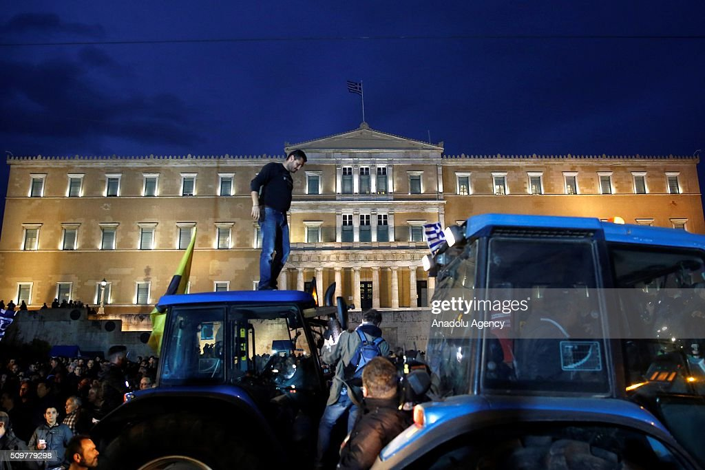 Farmers are seen near a tractor during a rally against pension reform in front of the Greek parliament at the Syntagma Square in Athens on February 12, 2016.