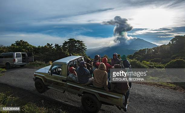 TOPSHOT Farmers are transported on the back of a truck as the Turrialba volcano erupts in the background on May 20 in Cartago Costa Rica The...