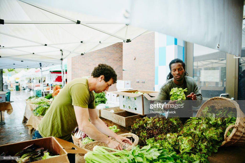 Farmers arranging vegetables at farmers market