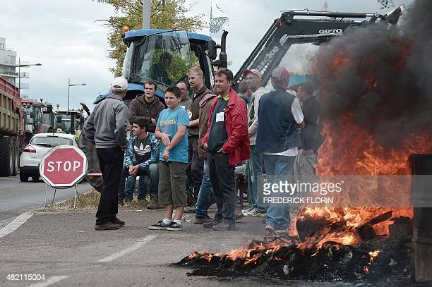 Farmers block access to vehicles as they protest on a bridge between France and Germany in Strasbourg eastern France on July 27 2015 The French...