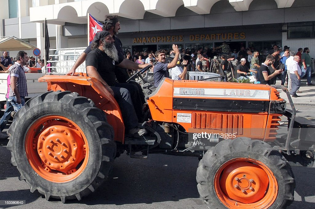 Farmers block the international airport of Heraclion with their tractors on October 4, 2012 on the Greek Island of Crete, to protest against new government austerity measuress. AFP PHOTO/ Costas Metaxakis