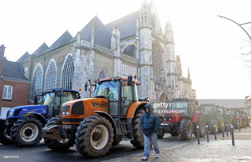 Farmers block the road with their tractors on January 2, 2014 in Dunkerque, northern France, during a demonstration called by the Gers farmers' union FDSEA to protest against the regional and ecological key measure of the Grenelle Environment, known as 'La Trame verte et bleue' (blue-green infrastructure).