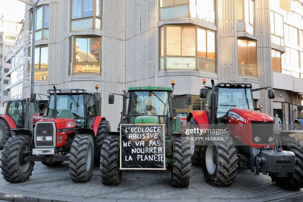 Farmers block the road with their tractors on January 2, 2014 in Dunkerque, northern France, during a demonstration called by the Gers farmers' union FDSEA to protest against the regional and ecological key measure of the Grenelle Environment, known as 'La Trame verte et bleue' (blue-green infrastructure). Sign (C) reads: 'Abusive ecology will not feed the planet'.