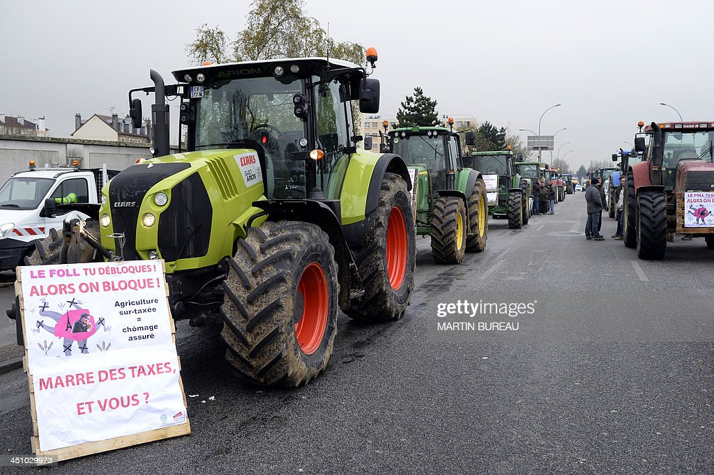 Farmers block the road with tractors in Trappes, near Paris, on November 21, 2013 to slow traffic during an 'operation escargot' (snail operation) called by the Ile-de-France farmers' union FDSEA to protest against higher tax rates and excess of regulations. The French government on November 21 ordered irate farmers blocking roads into Paris to halt their protest over tax hikes after accidents that left one person dead and six injured.