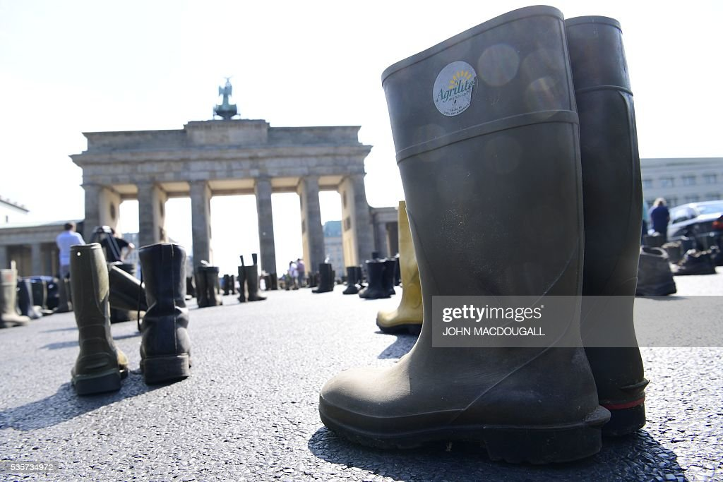 Farmers' boots are seen in front of the Brandenburg Gate in Berlin during a protest action of milk farmers association on May 30, 2016. German government meets today with representatives of the milk and retailing branches to discuss the milk prices among others items. / AFP / John MACDOUGALL