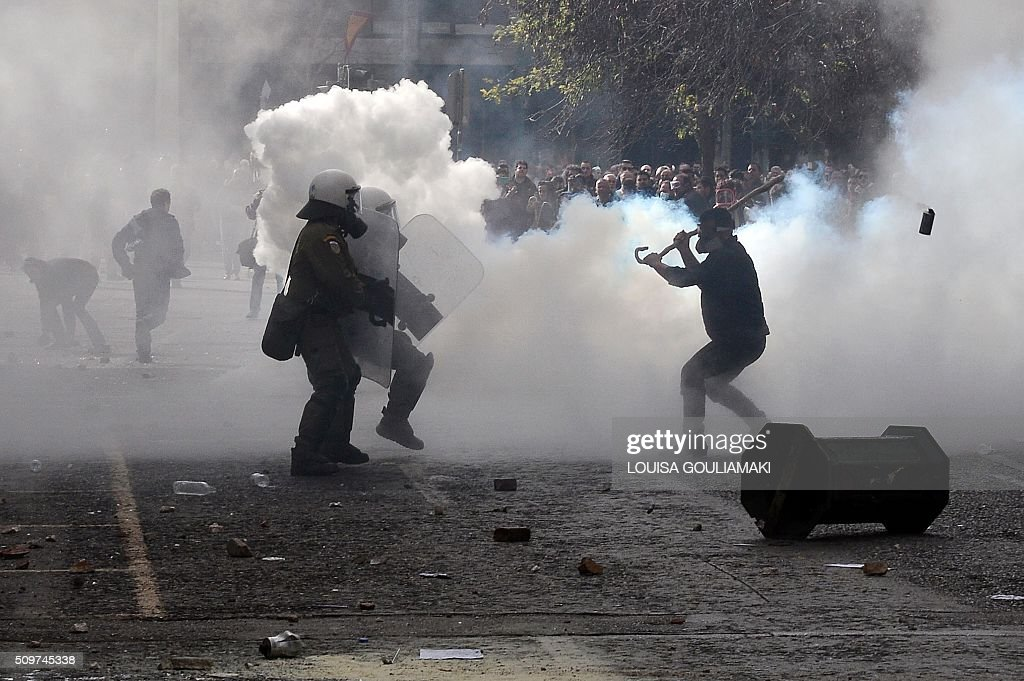 Farmers clash with police amid tear gas in front of the the Agriculture ministry in Athens, during a demonstration against the pension reform on February 12, 2016. Fears that Greece will exit the eurozone, a 'Grexit', could revive if Greek authorities do not come up with 'credible' reforms, notably on pensions, a senior IMF official said February 11, 2016. / AFP / LOUISA GOULIAMAKI