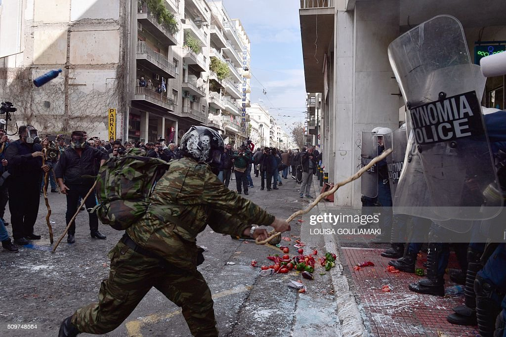 Farmers clash with police officers blocking the entrance of the Agriculture ministry in Athens, during a demonstration against pension reform on February 12, 2016. Fears that Greece will exit the eurozone, a 'Grexit', could revive if Greek authorities do not come up with 'credible' reforms, notably on pensions, a senior IMF official said February 11, 2016. / AFP / LOUISA GOULIAMAKI