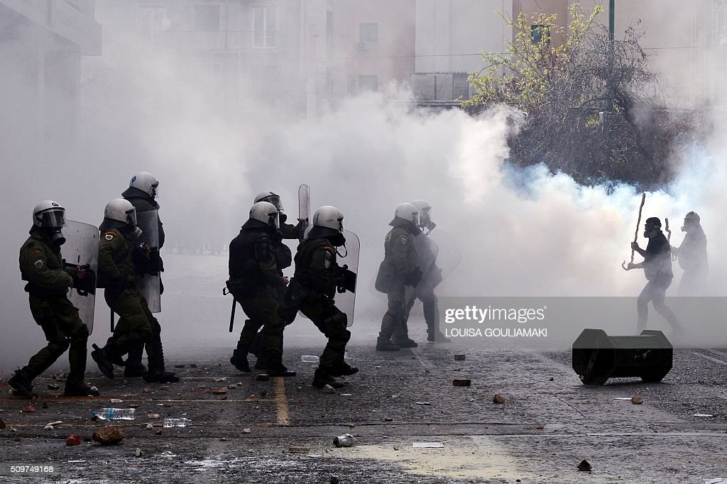 Farmers clash with police officers in front of the Agriculture ministry in Athens dukring a demonstration against the pension reform on February 12, 2016. Fears that Greece will exit the eurozone, a 'Grexit', could revive if Greek authorities do not come up with 'credible' reforms, notably on pensions, a senior IMF official said February 11, 2016. / AFP / LOUISA GOULIAMAKI