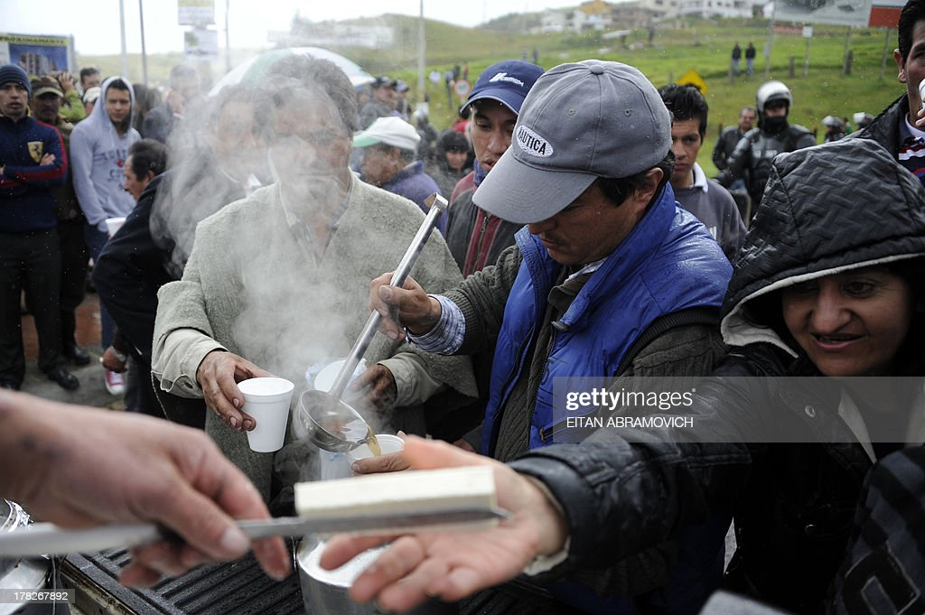 Farmers deliver free cheese and 'agua de panela' (a drink made with hot water and unrefined sugar) during a protest in La Calera, Cundinamarca department, Colombia, on August 28, 2013, in support of Colombian farmers on strike demanding government subsidies and greater access to land. AFP PHOTO/Eitan Abramovich