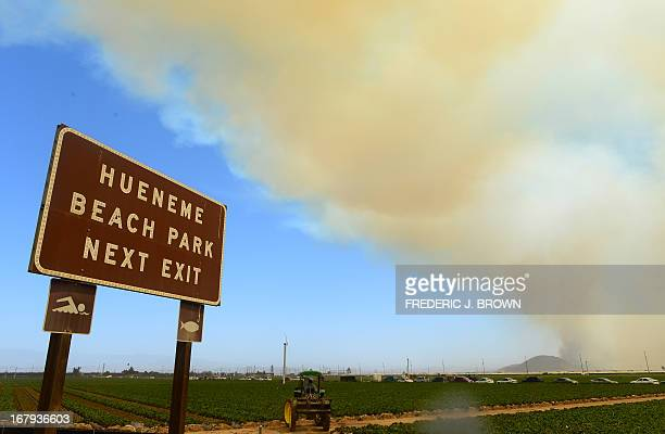 Farmers drive their tractors on farmland off the Pacific Coast Highway south of Oxnard as smoke rising into the sky and fanned by strong winds ravage...