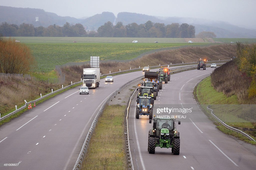 Farmers drive their tractors on the RN12 motorway in the Yvelines department in the French region of Ile-de-France on November 21, 2013 to slow down traffic during an 'operation escargot' (snail operation) called by the Ild-de-France farmers union FDSEA to protest against over taxing and the excess of regulations.