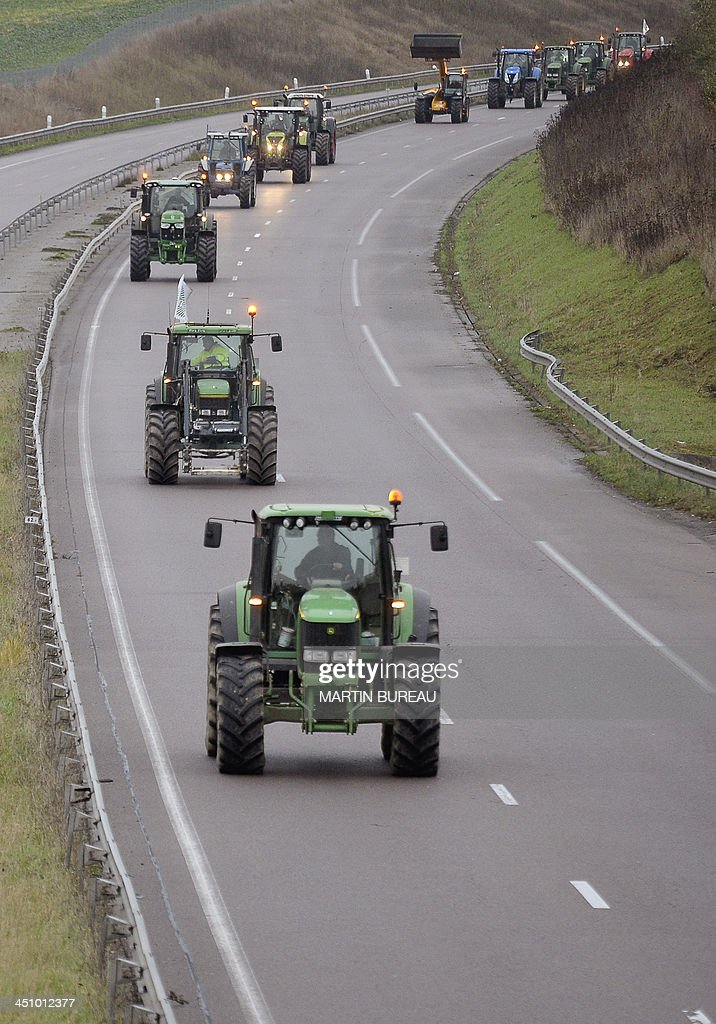 Farmers drive their tractors on the RN12 motorway in the Yvelines department in the French region of Ile-de-France on November 21, 2013 to slow down traffic during an 'operation escargot' (snail operation) called by the Ild-de-France farmers union FDSEA to protest against over taxing and the excess of regulations. AFP PHOTO / MARTIN BUREAU
