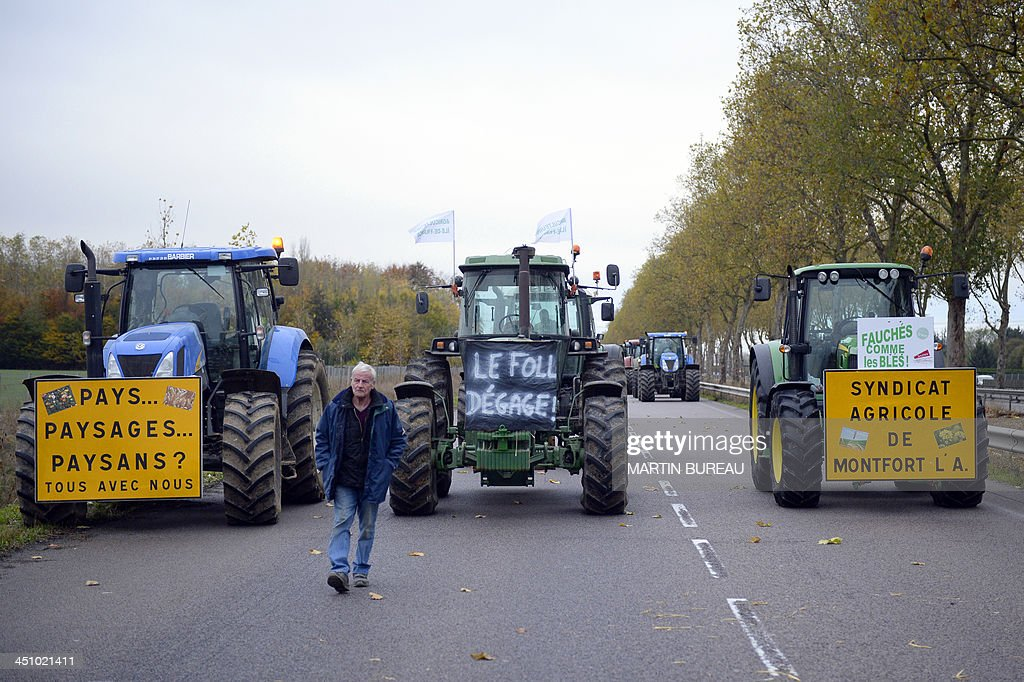 Farmers drive their tractors with placards reading 'countries, landscapes, farmers? all with us' (L), 'Le Foll go away' (C) - in reference to France's Agriculture Minister Stephane Le Foll - and 'cut like wheat, Agricultural union of Montfort' (expression meaning broke) on the RN12 motorway in the Yvelines department in the French region of Ile-de-France on November 21, 2013 to slow down traffic during an 'operation escargot' (snail operation) called by the Ild-de-France farmers union FDSEA to protest against over taxing and the excess of regulations.