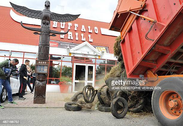 Farmers dump tires and hay in front of the restaurant Buffalo Grill in Metz eastern France on July 28 during a demonstration against falling food...