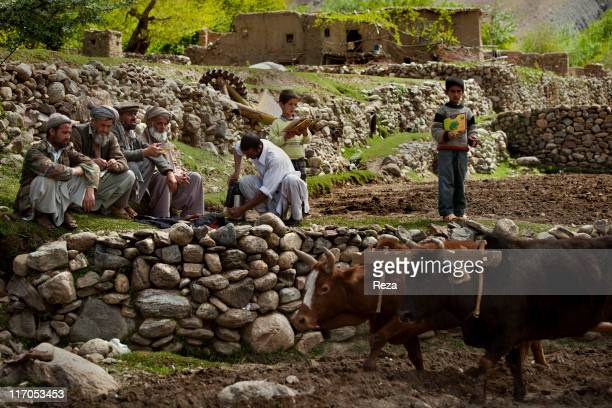 Farmers employing traditional agricultural methods having lunch while children are standing nearby holding copies of 'Parvaz' the children's magazine...