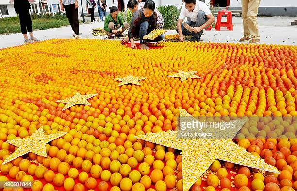Farmers form a Chinese flag with thousands of persimmons to celebrate the upcoming National Day at Lianshan village on September 29 2015 in Shangrao...