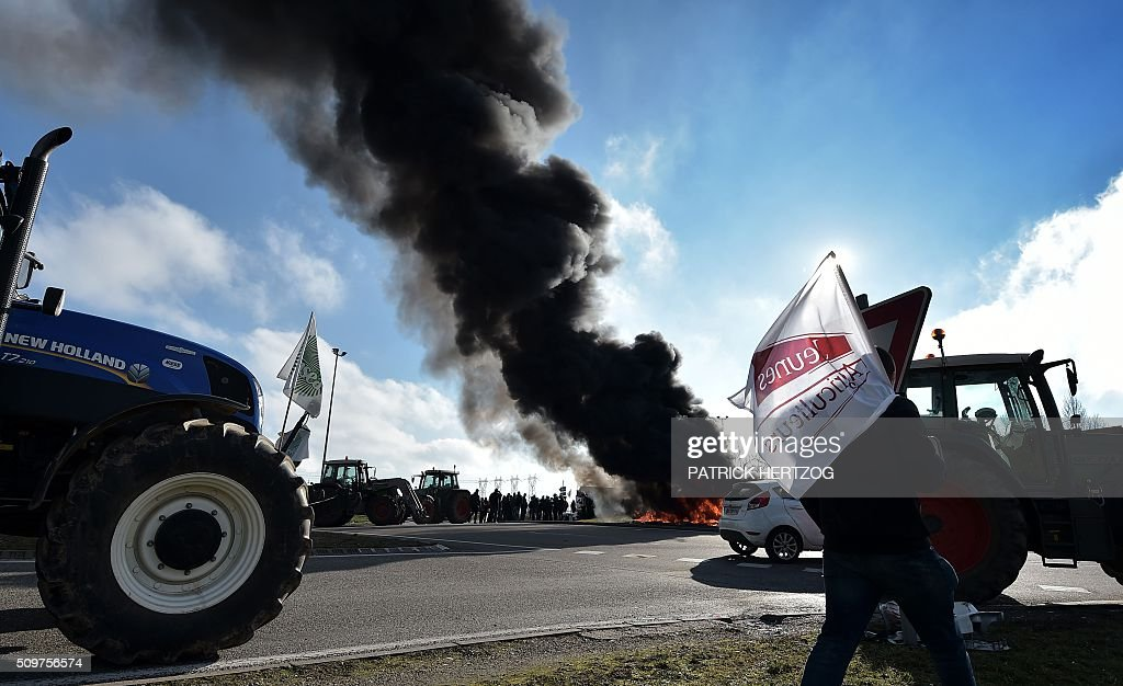 Farmers from the French farmers unions burn piles of tyres in Vendenheim, eastern France on February 12, 2016, protesting their increasing constraints and charges, the collapsing prices of cereals, milk and vegetables, caused in part by the sanctions on Russia, as well as rising fertiliser prices. / AFP / PATRICK HERTZOG