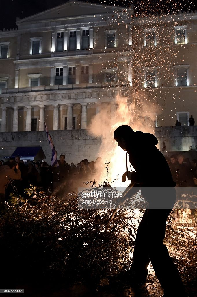 Farmers gather around a fire lit outside the Greek parliament during a protest against pension reform and tax issues, on February 12, 2016. Fears that Greece will exit the eurozone, a 'Grexit', could revive if Greek authorities do not come up with 'credible' reforms, notably on pensions, a senior IMF official said February 11. / AFP / ARIS MESSINIS
