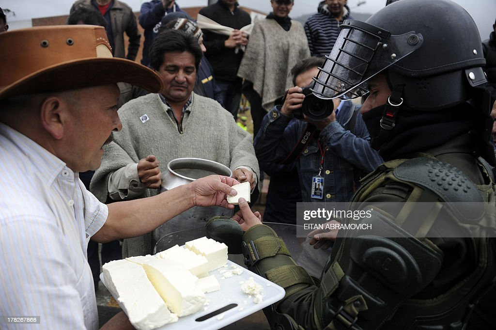 Farmers gives free cheese and 'agua de panela' (a drink made with hot water and unrefined sugar) to a riot policeman during a protest in La Calera, Cundinamarca department, Colombia, on August 28, 2013, in support of Colombian farmers on strike demanding government subsidies and greater access to land. AFP PHOTO/Eitan Abramovich