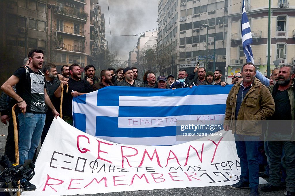 Farmers hold banners and shout slogans near the Agriculture ministry in Athens during a demonstration against the pension reform on February 12, 2016. Fears that Greece will exit the eurozone, a 'Grexit', could revive if Greek authorities do not come up with 'credible' reforms, notably on pensions, a senior IMF official said February 11, 2016. / AFP / LOUISA GOULIAMAKI