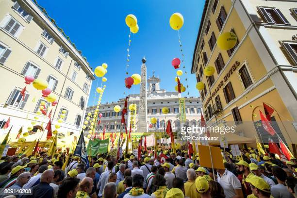 Farmers holds banner and flags of the ' Coldiretti ' association in front of the Italian Parliament as they demonstrate to ask the government to...