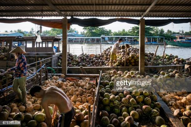 Farmers load up coconuts to a boat at a floating market on April 29 2017 in An Thanh Village Mo Cay Nam District Ben Tre Province Vietnam The Mekong...