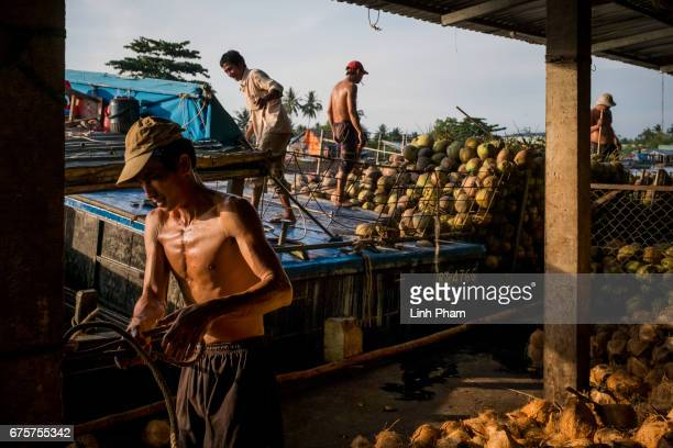 Farmers load up the coconut on the side of a floating market on May 2 2017 in An Thanh Village Mo Cay Nam District Ben Tre Province Vietnam The...