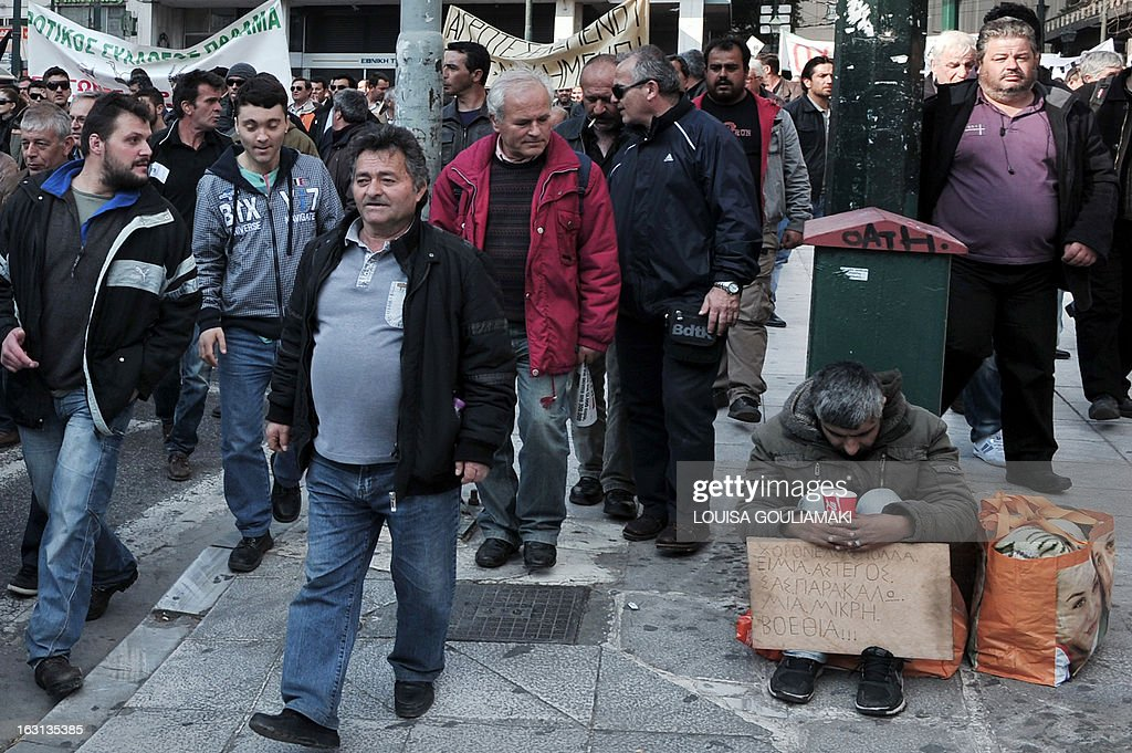 Farmers march by a homeless man near the Greek parliament in Athens during a protest by farmers' unions from all over Greece on March 5, 2013. Some 2,000 Greek farmers gathered in Athens to demand lower taxes, arguing that the rising cost of fuel and electricity was driving them to ruin.The farmers also called for subsidies from the heavily indebted state, which has been forced to undertake a tough austerity policy, to help them lower their costs and remain competitive.