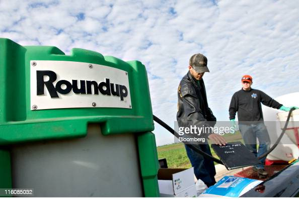 Farmers Matt Wiggeim right and Cody Gibson mix Monsanto Co's Roundup herbicide near a corn field in Kasbeer Illinois US on Monday June 13 2011 Corn...