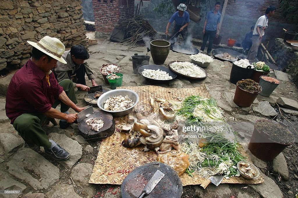 Farmers of the Yi ethnic group cook foods for a long-street banquet during a ceremony at the dragon festival on February 12, 2006 in Yuanyang County, Yunnan Province, China. During the festival, the Yi people get together to worship water, the dragon and heaven in expectations of a bumper grain harvest and favorable weather for the coming year. At the banquet, each household contributes to the preparation of Yi style chicken, fish, and minced pork dishes. These are placed on a 700-meter-long chain of tables from each household in the main street.