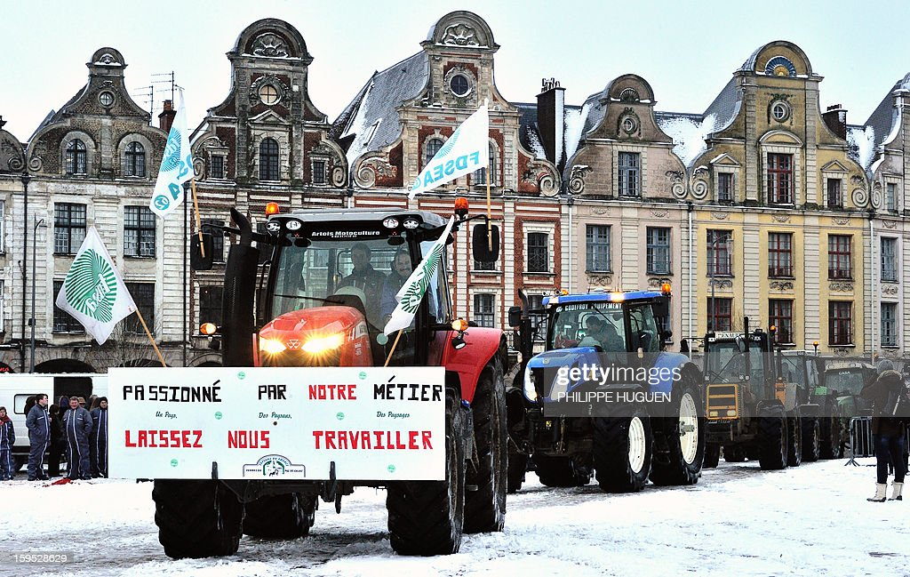 Farmers on a tractor with letters reading 'Our job is our passion, Let us work' take part in a partial blockade with some hundred tractors, on January 15, 2013 at the Grand'place in Arras, in northern France, during a demonstration called by farmers local union FDSEA, to denounce all kinds of pressure affecting their activities.