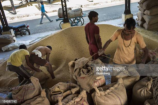 Farmers pack soybeans in gunny sacks to be sold at a grain market in Burhanpur Madhya Pradesh India on Friday Oct 19 2012 Global soybean consumption...